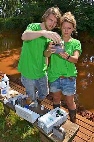 Charlene Fuchs und Patrick Held, ehrenamtliche Greenpeace-Helfer, schauen sich die Messproben aus der Wuderitz bei Ragow an.