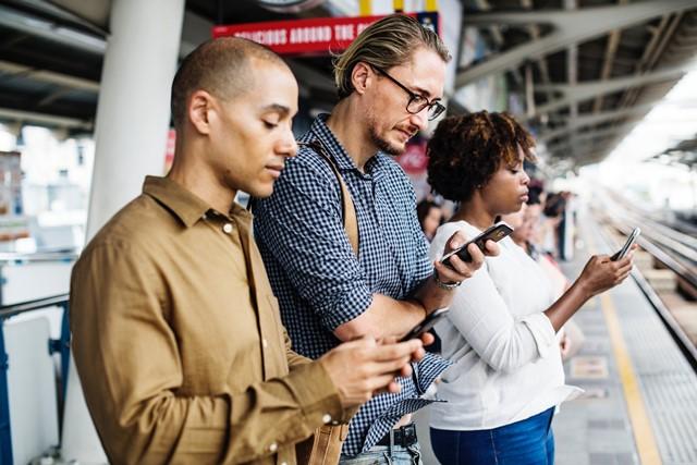 Drei Personen mit Smartphone